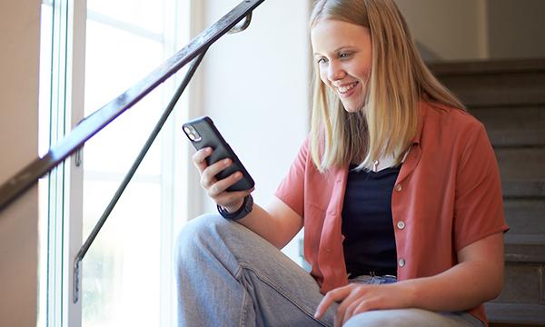 Flicka med ljust hår sitter i ett fönster och tittar på mobilen.